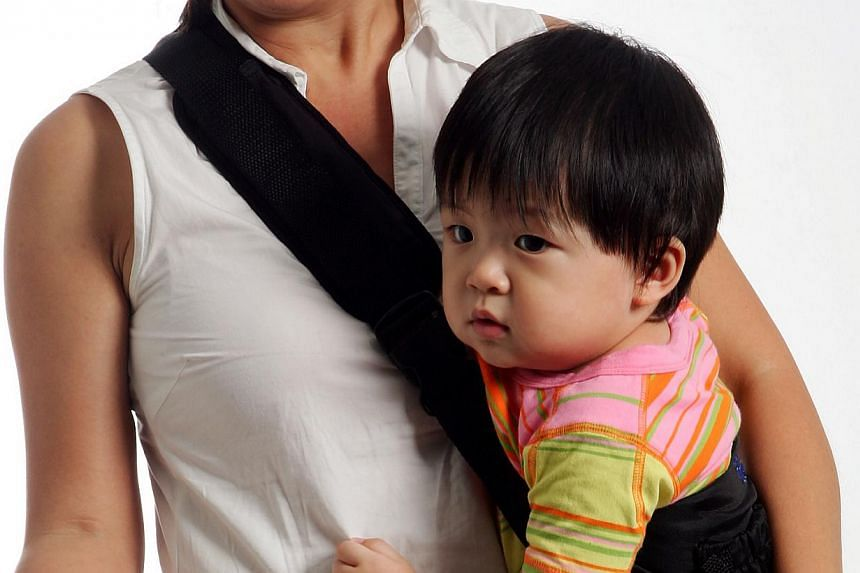 Posed photo of a woman carrying a baby. There were 42,663 babies born in Singapore last year, but only half of them had parents who were both Singapore citizens. Their proportion of all births shrank sharply from 2000. -- ST FILE PHOTO: LAU FOOK KONG
