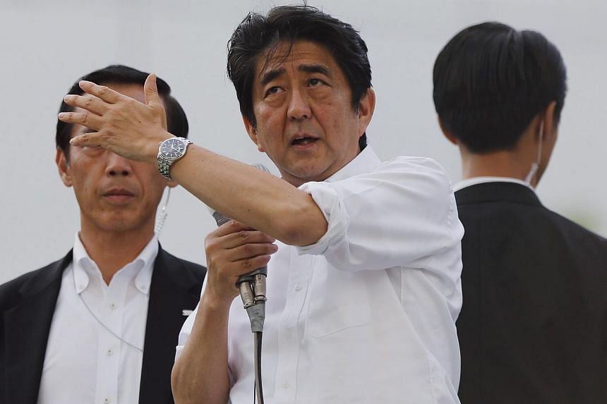 Japan's Prime Minister Shinzo Abe (centre), and the leader of the ruling Liberal Democratic Party (LDP), gestures to voters atop a van while campaigning for the July 21 Upper house election in Tokyo on July 20, 2013. Japanese voters go to the polls o
