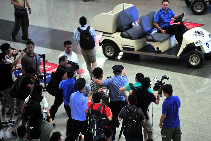 Chinese security personnel prevent media members from getting closer to the scene where a man in a wheelchair ignited a home-made explosive device at Beijing's international airport terminal 3 on July 20, 2013, injuring himself but no others. Chinese