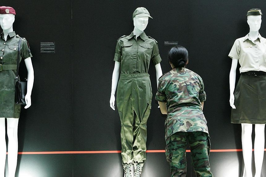 A female SAF officer scrutinises one of the uniforms on display at Mindef's first ever exhibition on the achievements and contributions of women in the Singapore Armed Forces in this June 4, 2007 file photo. The SAF is looking for more women to join