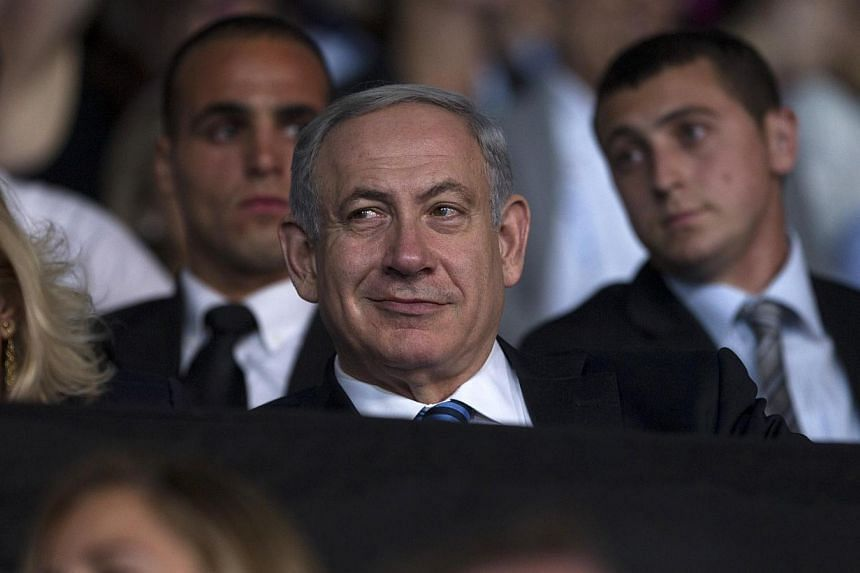 "Israel's Prime Minister Benjamin Netanyahu smiles during the opening ceremony of the 19th Maccabiah Games at Teddy Stadium in Jerusalem on July 18, 2013. Renewing negotiations with the Palestinians is ""vital"" for Israel, Prime Minister Benjamin Netan"
