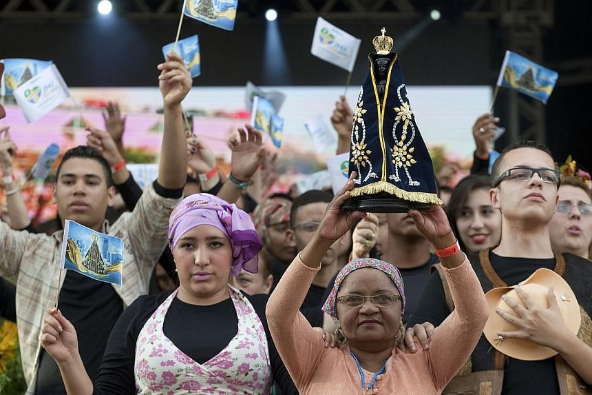 A woman holds up a replica of the statue of Our Lady of Aparecida during a special Catholic Mass ahead of World Youth Day in Sao Paulo, Brazil, Saturday, July 20, 2013. Pope Francis will travel to Brazil and participate in WYD events from July 22-28.