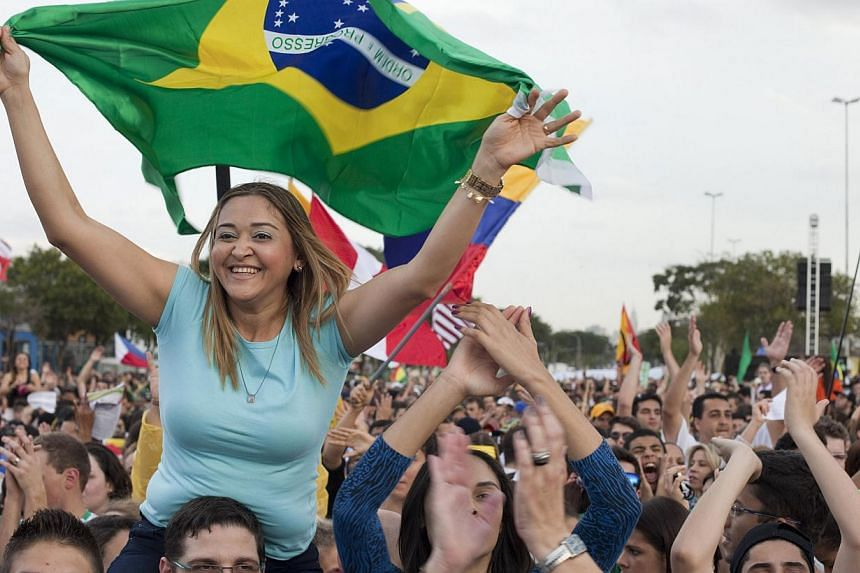 A Catholic woman waves a Brazilian flag as she attends a special Mass ahead of World Youth Day in Sao Paulo, Brazil, Saturday, July 20, 2013. Pope Francis will travel to Brazil and participate in WYD events from July 22-28. -- PHOTO: AP