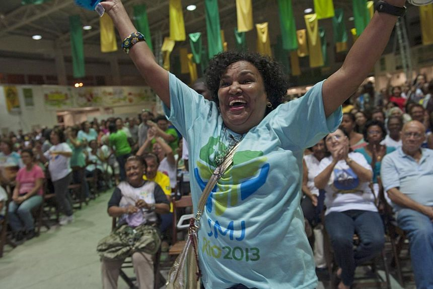A Catholic woman jumps and shouts as the World Youth Day Cross is brought into a samba school in Rio de Janeiro, Brazil, July 20, 2013. The WYD symbol was given to young people of the church in 1983 by the architect of WYD, Pope John Paul II. Pope Fr
