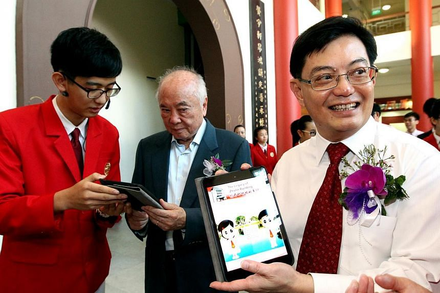 Mr Heng (right) and school management committee chairman Wee Cho Yaw learning about Chung Cheng High School (Main)'s new mobile app.