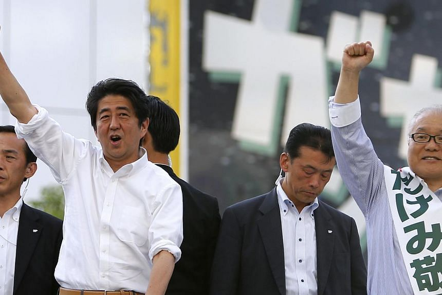 Japan's Prime Minister Shinzo Abe (second from left), and the leader of the ruling Liberal Democratic Party (LDP), raises his fist atop a van while campaigning in Tokyo on July 20, 2013. The coalition of Japan's Prime Minister Shinzo Abe won a resoun