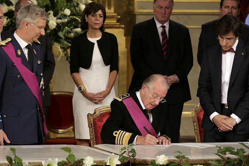 King Albert II (centre) of Belgium, watched by his son Crown Prince Philippe (left) and Belgium's Prime Minister Elio Di Rupo (right), signs an act of abdication during a ceremony at the Royal Palace on Belgian National Day in Brusselson Sunday