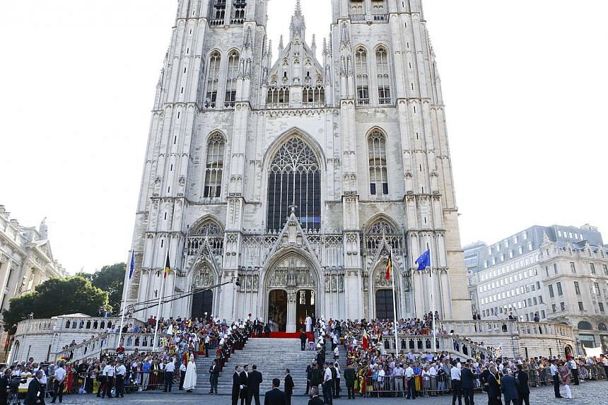 People stand outside St Gudule Cathedral during a Te Deum mass celebrating the 20th anniversary of the reign of Belgium's King Albert II, the Belgian National Day, King Albert's abdication and the inauguration of his successor King Philippe in Brusse