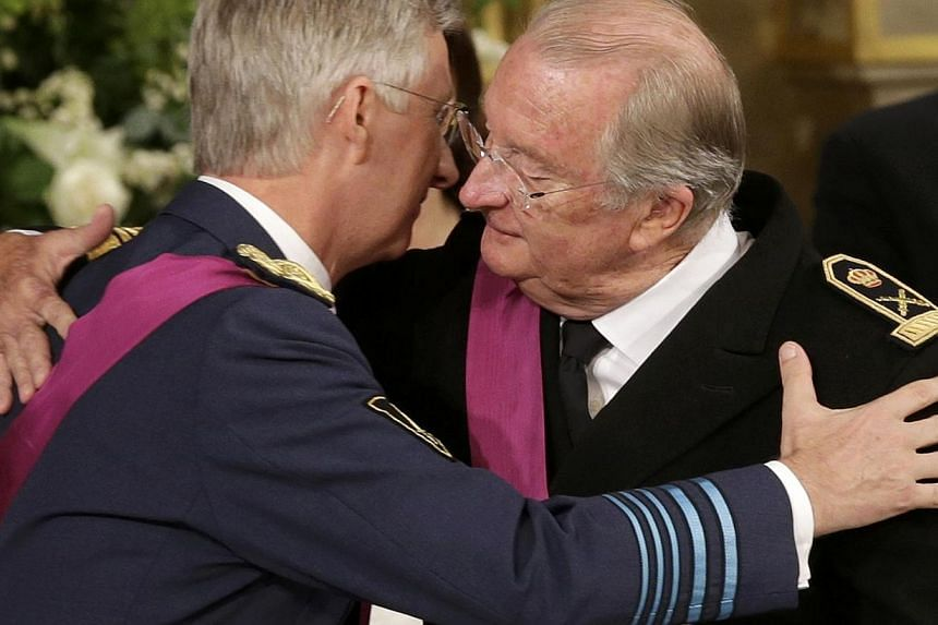 Belgium's Crown Prince Philippe (left) hugs his father King Albert II during the King's abdication ceremony at the Royal Palace on Belgian National Day in Brussels on Sunday, July 21, 2013. Albert II abdicated on Sunday after 20 years as 'King of the