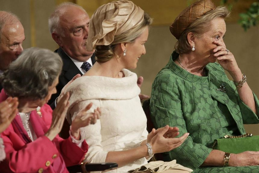 Belgium's Queen Paola (right) reacts as Crown Princess Mathilde (centre) and Queen Fabiola applaud while King Albert II signs an act of abdication during a ceremony at the Royal Palace on Belgian National Day in Brussels on Sunday, July 21, 2013. Alb