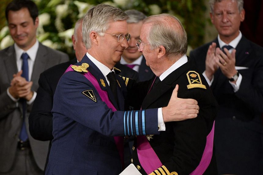Crown Prince Philippe of Belgium (left) and King Albert II of Belgium embrace during the signing of the abdication treaty on the occasion of Belgian National Day, at the Royal Palace in Brussels on Sunday, July 21, 2013. Albert II abdicated on Sunday