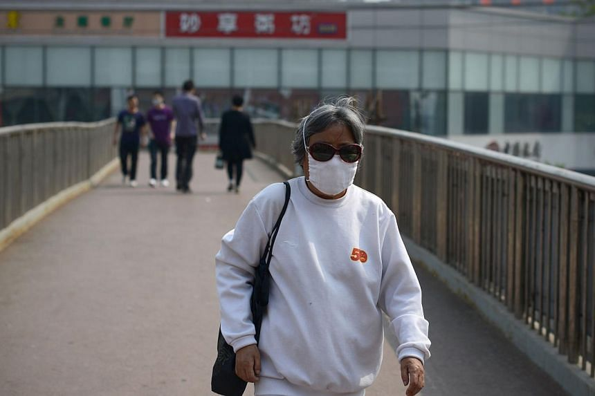 An elderly woman wears a face mask as she walks on an overpass in Beijing on May 2, 2013. A 61-year-old woman from northern China was confirmed on Saturday as having contracted the deadly H7N9 bird flu virus, state media reported. -- PHOTO: AFP