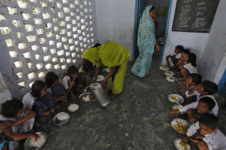 A cook serves the free mid-day meal, distributed by a government-run primary school, to children at Brahimpur village in Chapra district of the eastern Indian state of Bihar on July 19, 2013. The free school lunch that killed 23 Indian children last
