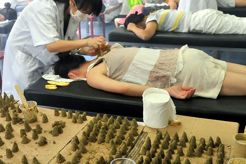 "Patients undergoing TCM treatment from putting a box-like contraption containing herbal remedies on their heads, to acupuncture and sticking herbal patches to their chests. These are part of the procedures, dubbed ""san fu tie"" to ""cure winter ailment"