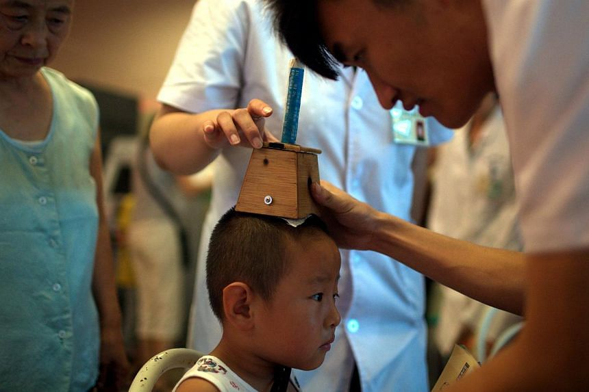 """Children undergoing TCM treatment from putting a box-like contraption containing herbal remedies on their heads, to acupuncture and sticking herbal patches to their chests. These are part of the procedures, dubbed """"san fu tie"""" to """"cure winter ailment"""