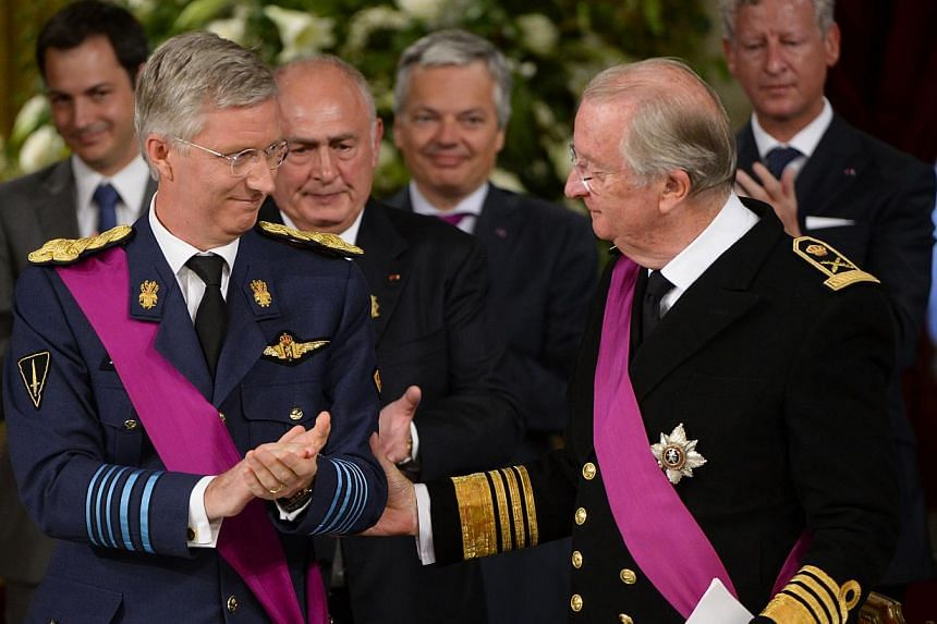 King Albert II of Belgium (right) congratulate Crown Prince Philippe of Belgium during the signing of the abdication treaty on the occasion of Belgian National Day, at the Royal Palace in Brussels on Sunday, July 21, 2013. Philippe ascended to the th