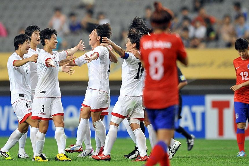 North Korean players celebrate their victory against South Korea after the Women's East Asian Cup football match at Seoul World Cup stadium in Seoul on Sunday, July 21, 2013. North edged out South 2-1 in an inter-Korean football showdown at the Women