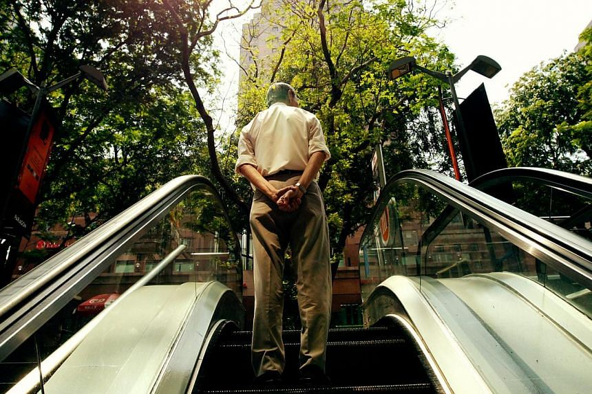 An elderly person goes up the escalator. The private sector has done well in remunerating older, re-employed workers, a survey by the National Trades Union Congress has shown. -- BT FILE PHOTO: YEN MENG JIIN