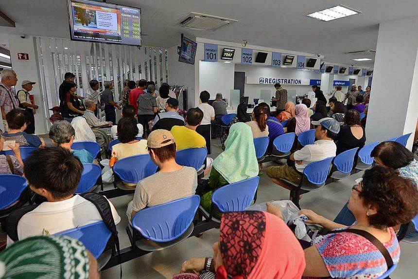 Patients waiting inside SingHealth polyclinic at Tampines. The Ministry of Manpower (MOM) has told employers not to influence doctors to give injured workers less sick leave than they need. -- ST FILE PHOTO: RAJ NADARAJAN