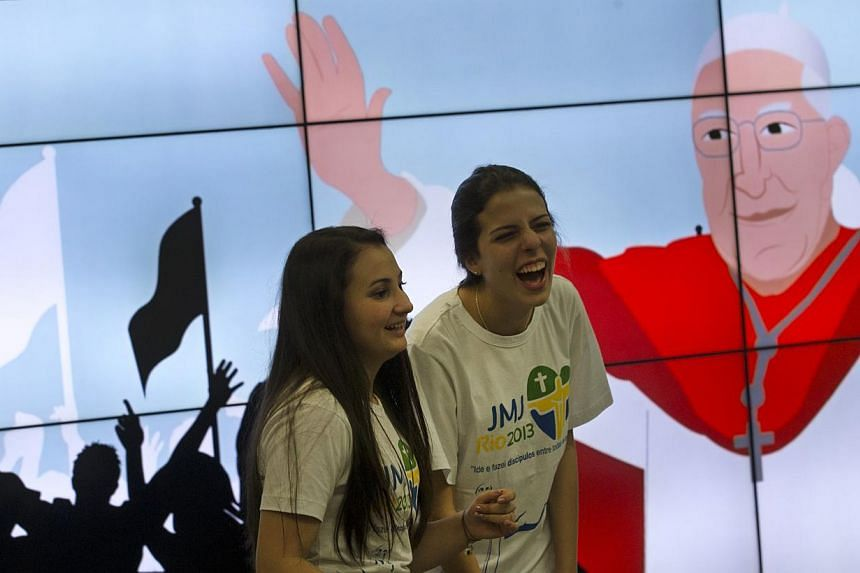 Young pilgrims laugh in front of screen featuring a drawing of Pope Francis at the international airport in Rio de Janeiro, Brazil, Friday, July 19, 2013. -- PHOTO: AP