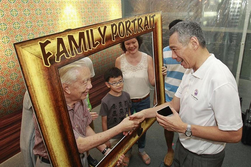 Prime Minister Lee Hsien Loong shakes the hand of Mr Yuen Ngok Onn, 79, after helping to take a polaroid picture of his family during Singapore Heritage Fest's 10th anniversary celebrations at the National Museum of Singapore on Sunday, July 21, 2013