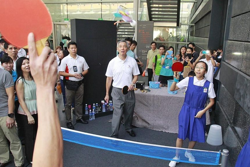 Prime Minister Lee Hsien Loong takes part in a game of ping-pong chapteh with students from CHIJ St Nicholas Girls School during Singapore Heritage Fest's 10th anniversary celebrations at the the National Museum of Singaporeon Sunday, July 21,