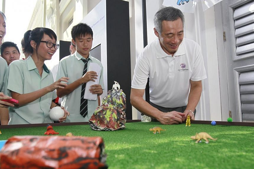 Prime Minister Lee Hsien Loong flicks a marble past obstacles and towards a hole on a Jurassic Park-themed game during Singapore Heritage Fest's 10th anniversary celebrations at the the National Museum of Singapore on Sunday, July 21, 2013. A ne