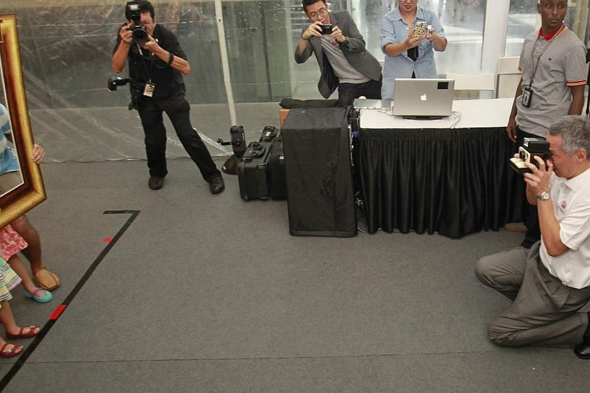 Prime Minister Lee Hsien Loong takes a polaroid picture of a family during Singapore Heritage Fest's 10th anniversary celebrations at the National Museum of Singaporeon Sunday, July 21, 2013. A new $5-million grant to encourage Singaporeans to