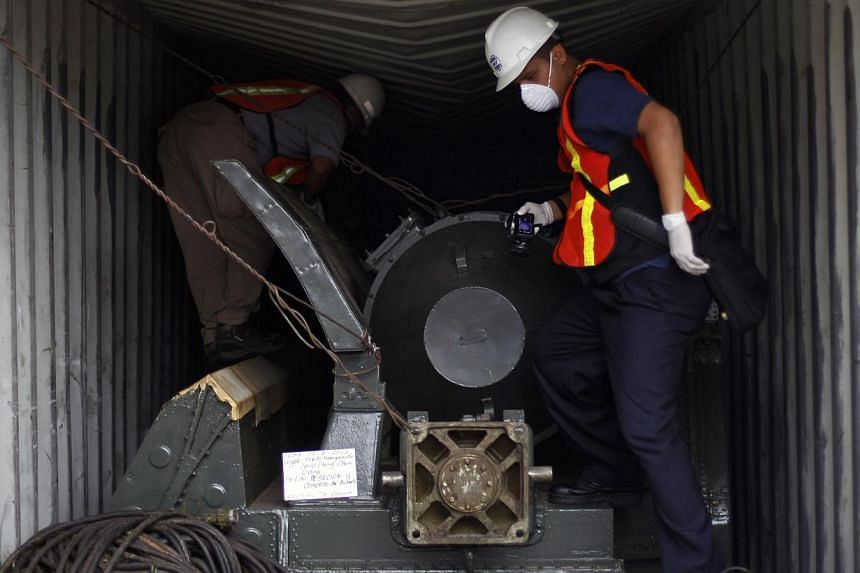 """Panama forensic workers work in a container holding a green missile-shaped object seized from the North Korean flagged ship """"Chong Chon Gang"""" at the Manzanillo Container Terminal in Colon City on July 17, 2013. UN Secretary-General Ban Ki Moon praise"""