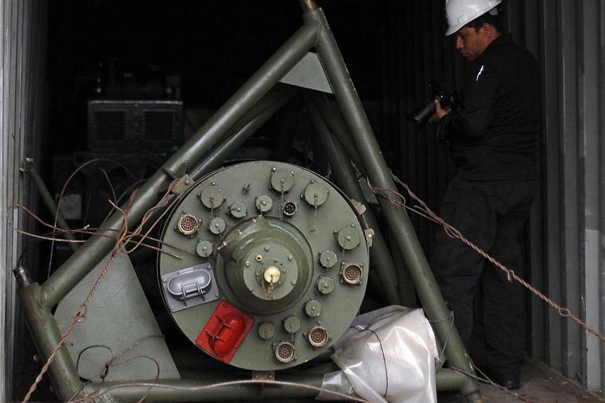 """A Panama forensic worker works in a container holding a green missile-shaped object seized from the North Korean flagged ship """"Chong Chon Gang"""" at the Manzanillo Container Terminal in Colon City on July 17, 2013. UN Secretary-General Ban Ki Moon prai"""