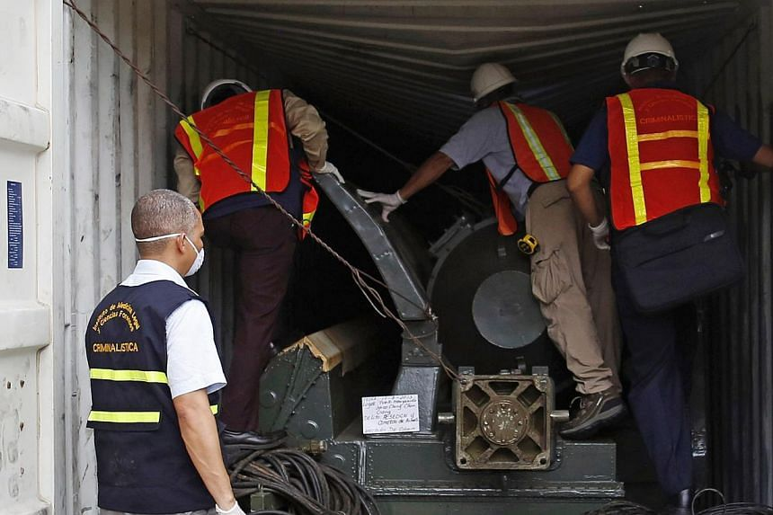 """Panama forensic workers work in a container holding a missile-shaped object seized from the North Korean flagged ship """"Chong Chon Gang"""" at the Manzanillo Container Terminal in Colon City on July 17, 2013. UN Secretary-General Ban Ki-moon praised Pana"""
