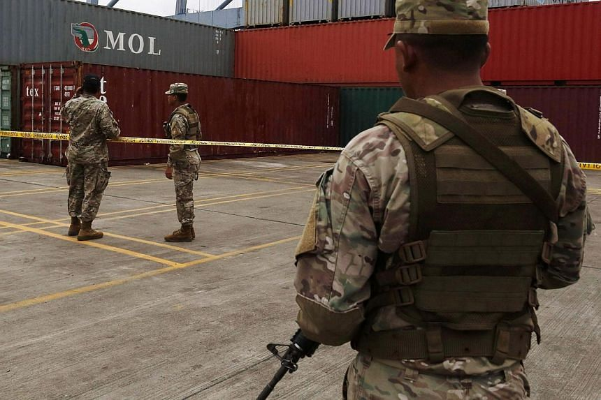 """Soldiers stand guard near containers holding arms seized from the North Korean flagged ship """"Chong Chon Gang"""" at the Manzanillo Container Terminal in Colon City on July 17, 2013. UN Secretary-General Ban Ki Moon praised Panama on Wednesday for seizin"""