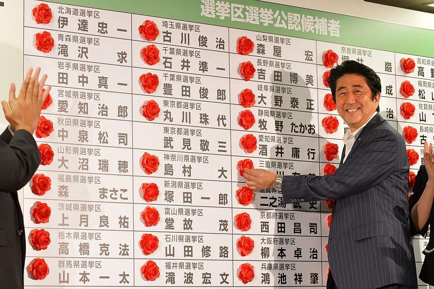 Japan's Prime Minister and President of the Liberal Democratic Party (LDP), Shinzo Abe (centre) smiles as he places a red paper rose on a LDP candidate's name to indicate an election victory at the party's headquarters in Tokyo on July 21, 2013.&nbsp