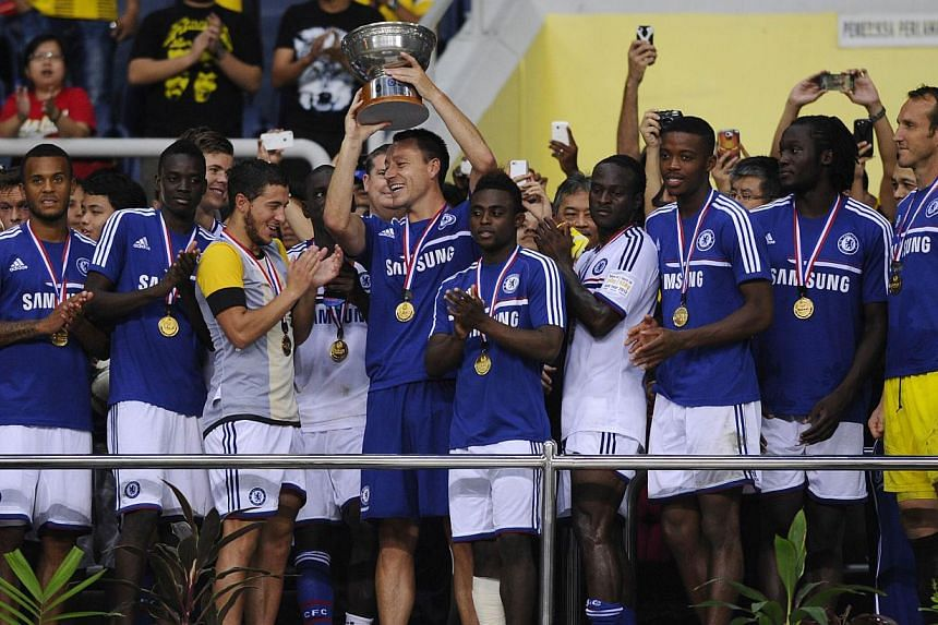 Chelsea football player John Terry (centre) and his teammates celebrate with the trophy after a friendly football match between English Premier League Chelsea and Malaysia XI at the Shah Alam Stadium in Shah Alam, outside Kuala Lumpur on July 21, 201