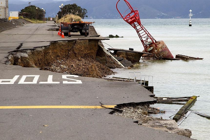 A bout that used to be on the edge of the road sits in the harbour where the land fell into the sea at the Port Wellington Container terminal caused by Sunday's earthquake on July 22, 2013. -- PHOTO: AFP