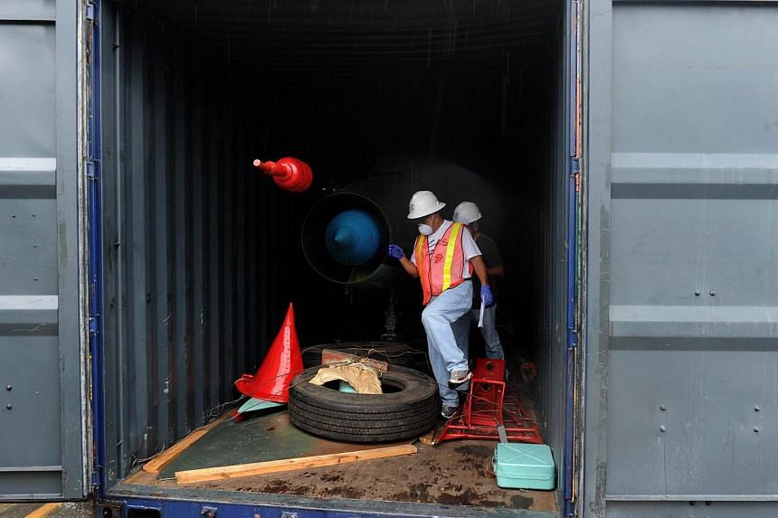 Men work in a container with the MIG-21 jets found inside the North Korean Chong Chon Gang vessel where an alleged Soviet-built radar control system for surface-to-air missiles was found, at the Manzanillo Port in Colon, 90 km from Panama City, on Ju