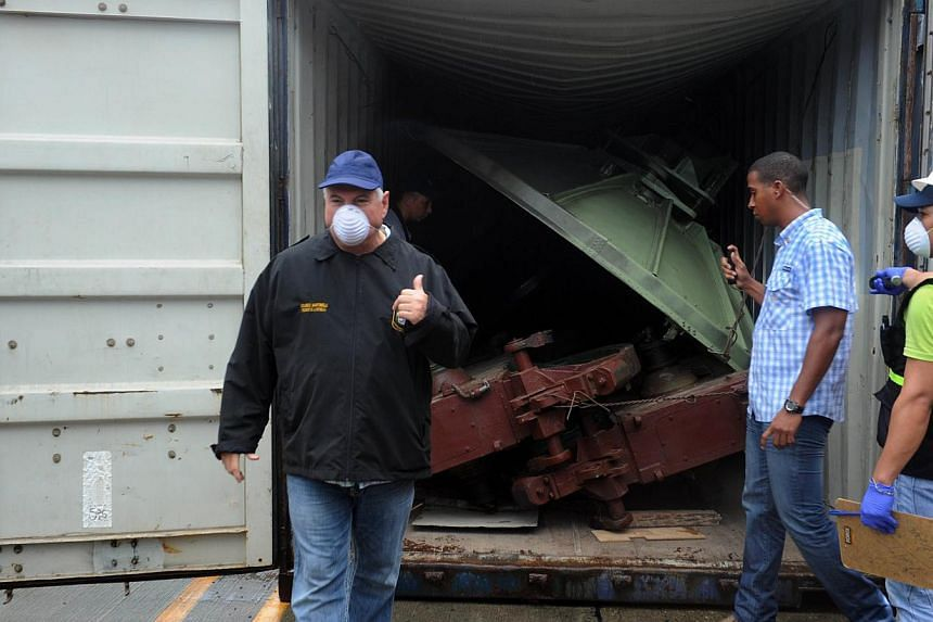Panamanian President Ricardo Martinelli (left) gesture next to a container with the MIG-21 jets found inside the North Korean Chong Chon Gang vessel where an alleged Soviet-built radar control system for surface-to-air missiles was found, at the Manz