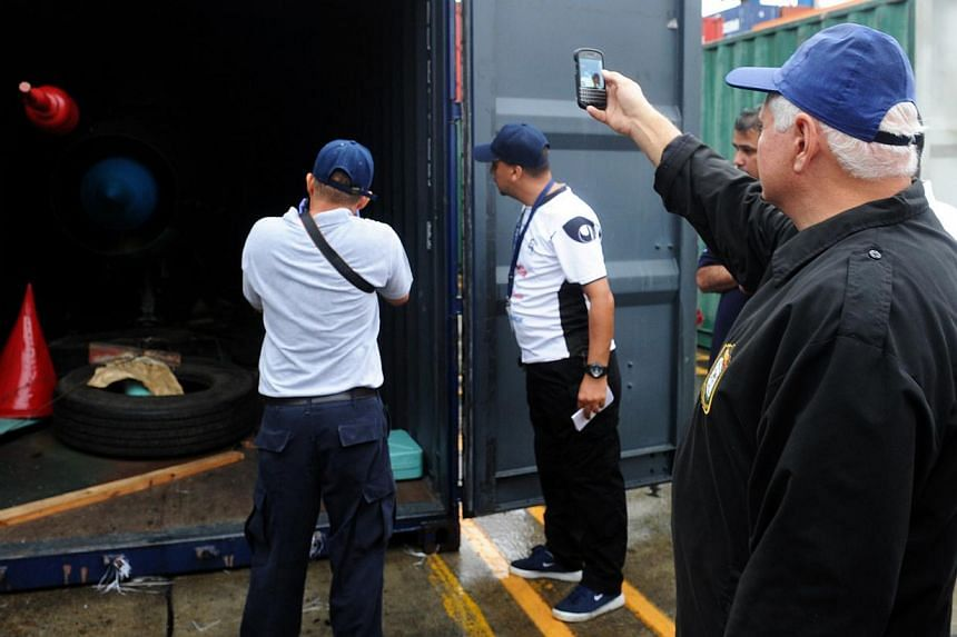 Panamanian President Ricardo Martinelli (right) takes a picture of a container with the MIG-21 jets found inside the North Korean Chong Chon Gang vessel where an alleged Soviet-built radar control system for surface-to-air missiles was found, at the