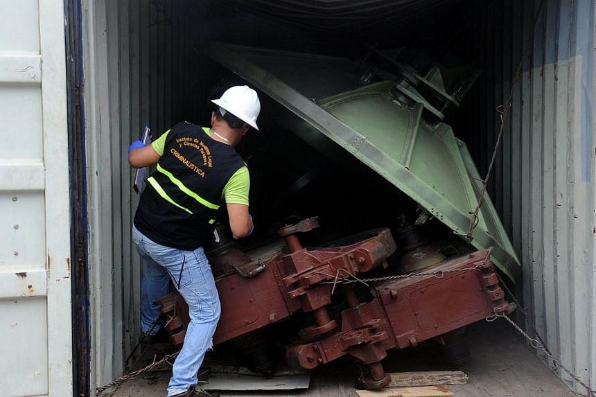 A man works in a container with the MIG-21 jets found inside the North Korean Chong Chon Gang vessel where an alleged Soviet-built radar control system for surface-to-air missiles was found, at the Manzanillo Port in Colon, 90km from Panama City, on