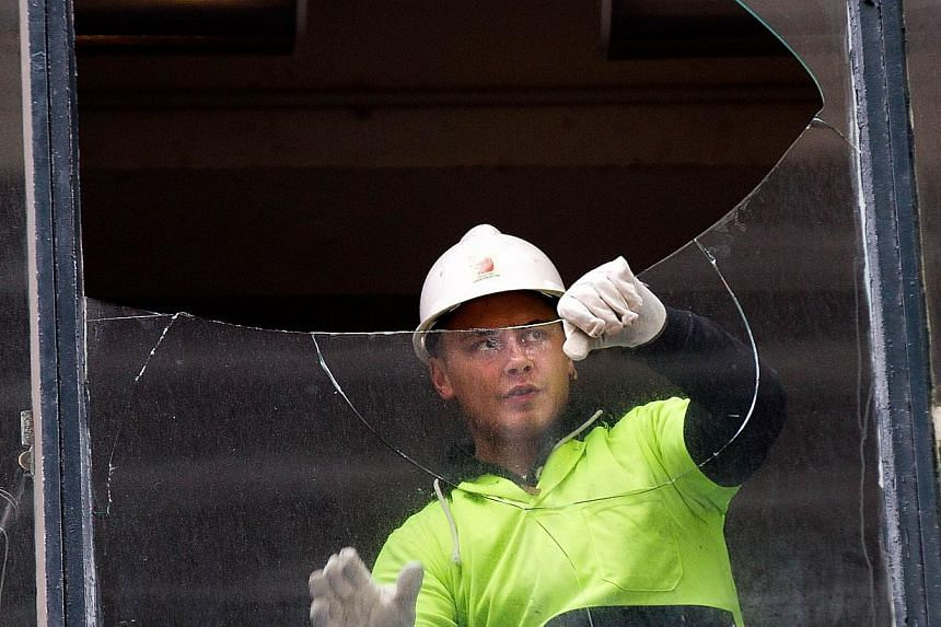 A glazier repairs broken windows in Wellington on July 22, 2013 following an earthquake on July 21. -- PHOTO: AFP
