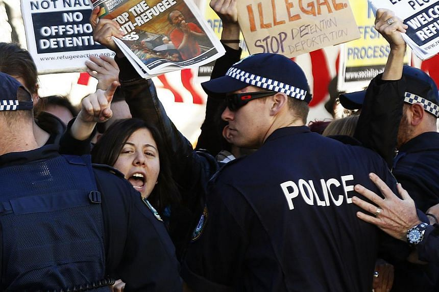 A woman shouts slogans against the Australian Labor Party (ALP) during a rally in support of asylum seekers outside an ALP meeting in Sydney on July 22, 2013. Australia's new policy of resettling refugees in Papua New Guinea was already having a dete