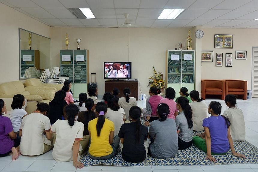 Indonesian maids watching television at the Indonesian Embassy's shelterfor runaway maids. Most of the maids in the shelter today are there not so much by choice but because they are owed salaries by their employers, or are involved in police cases i
