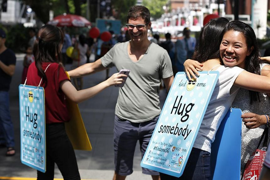 """Ngee Ann Polytechnic students offering free hugs at a """"kind zone"""" they set up outside Wisma Atria on Saturday. They also handed out handwritten notes asking people to be kinder to others. -- PHOTO: DESMOND LUI FOR THE STRAITS TIMES"""