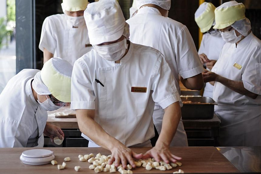 Employees at Ding Tai Fung's BreadTalk Mall is seen working through a window on Monday, July 22, 2013. When labour chief Lim Swee Say goes to Chinese restaurant Din Tai Fung, his eyes are peeled not so much on its dumplings and noodles, but on i