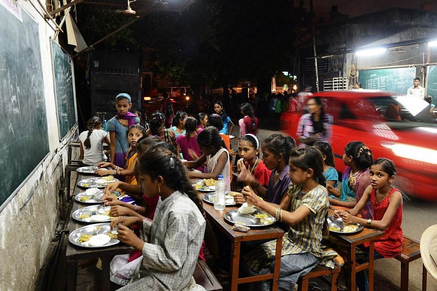 """Indian students eat a meal at the Footpath School in Ahmedabad on July 20, 2013. The pesticide that killed 23 Indian schoolchildren last week is a nerve poison banned by many countries because of what the World Health Organisation describes as its """"h"""