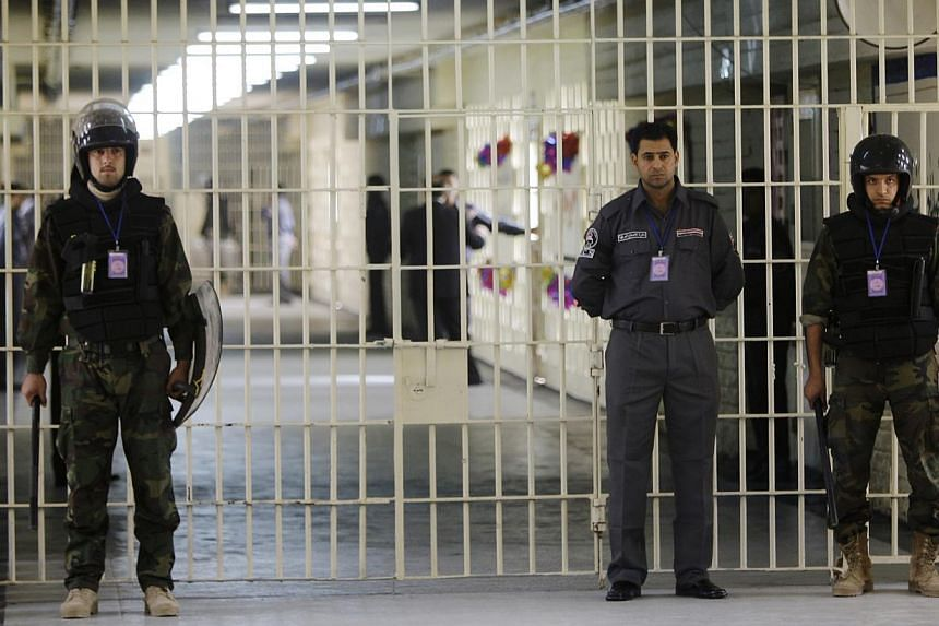 Guards stand at a cell block at the renovated Abu Ghraib prison in Baghdad, Iraq on Feb 21, 2009. Iraqi militants stormed two prisons, including the notorious Abu Ghraib, sparking clashes that killed 41 people and freeing at least 500 inmates, offici