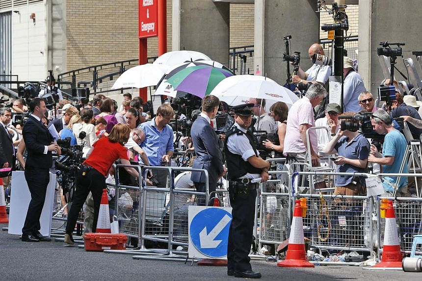 Members of the media wait outside St Mary's Hospital exclusive Lindo Wing in London on Monday, July 22, 2013. The London hospital hosting Prince William's wife Kate was the scene of a media frenzy on Monday after weeks of waiting for the royal baby -