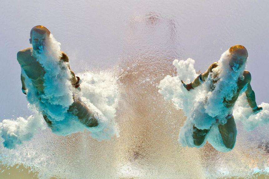 In a picture taken with an underwater camera, US diver David Bonuchi and Toby Stanley enter the water as they compete in the men's 10-metre synchro platform preliminary diving event in the Fina World Championships at the Piscina Municipal de Montjuic