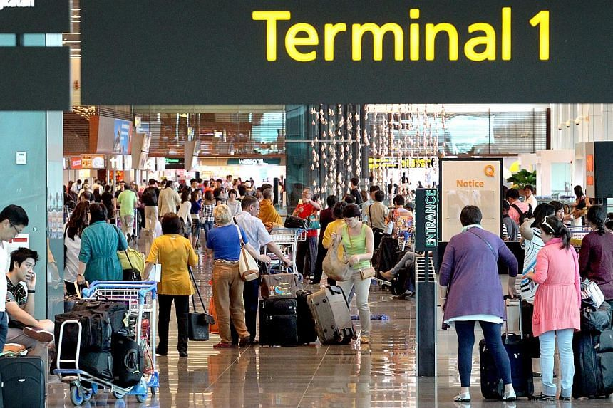Passengers at Changi Airport Terminal 1. Changi Airport handled 4.67 million passengers in June, 6.1 per cent more than in the same month last year. -- ST FILE PHOTO: CHEW SENG KIM