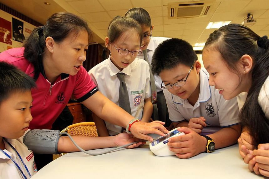 A parent volunteer (second from left) showing the pupils from Naval Base Primary School how to use a blood pressure monitor during a BP Initiative @Schools programme. Some parent volunteers have put in up to 80 hours of volunteer work, but despite th